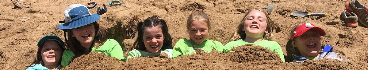 Kids buried in sand during Outdoor Camp
